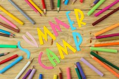 Text SUMMER CAMP of multicolored paper letters and color pencils on a natural wooden background. top view. flat lay royalty free stock photos