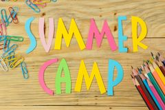 Text SUMMER CAMP of multicolored paper letters and color pencils on a natural wooden background. top view. flat lay stock image