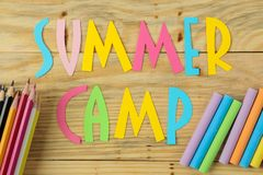 Text SUMMER CAMP of multicolored paper letters and color pencils on a natural wooden background. top view. flat lay stock photo