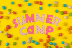 Text SUMMER CAMP of multicolored paper letters and colored candies on a bright yellow background. top view. flat lay royalty free stock photos