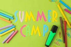 Text SUMMER CAMP of multicolored paper letters and colored crayons on a bright green background. top view. flat lay. Text SUMMER CAMP of multicolored paper stock image