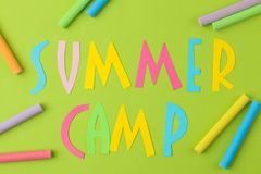 Text SUMMER CAMP of multicolored paper letters and colored crayons on a bright green background. top view. flat lay stock photo