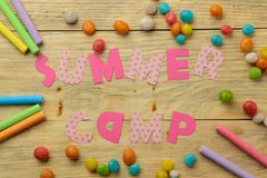 Text SUMMER CAMP of multicolored paper letters and colored crayons and candies on a natural wooden background. top view. flat lay royalty free stock photos