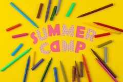 Text SUMMER CAMP of multicolored paper letters and colored felt-tip pens on a bright yellow background. top view. flat lay royalty free stock photo