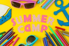 Text SUMMER CAMP of multicolored paper letters and colored felt-tip pens on a bright yellow background. top view. flat lay stock photo