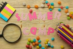 Text SUMMER CAMP of multicolored paper letters and colored pencils and candies on a natural wooden background. top view. flat lay stock photo