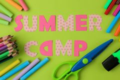 Text SUMMER CAMP of multicolored paper letters and crayons, pencils on a bright green background. top view. flat lay stock image