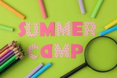 Text SUMMER CAMP of multicolored paper letters and crayons, pencils on a bright green background. top view. flat lay royalty free stock photo