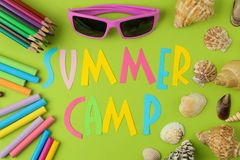 Text SUMMER CAMP of multicolored paper letters and crayons, pencils and seashells on a bright green background. top view. flat lay. Text SUMMER CAMP of stock photo