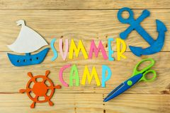 Text SUMMER CAMP of multicolored paper letters and decorative marine steering wheel and anchor on a natural wooden background. top. View. flat lay royalty free stock photography