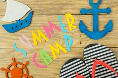 Text SUMMER CAMP of multicolored paper letters and decorative marine steering wheel and anchor on a natural wooden background. top. View. flat lay royalty free stock image