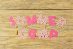 Text SUMMER CAMP of multicolored paper letters on natural wooden background. Top view. flat lay royalty free stock photos