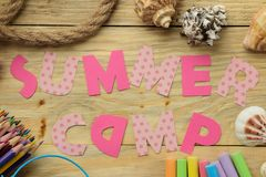 Text SUMMER CAMP of multicolored paper letters and rope and colored chalk on a natural wooden background. top view. flat lay stock photo
