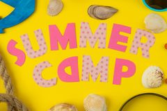 Text SUMMER CAMP of multicolored paper letters and sea elements on a bright yellow background. top view. flat lay royalty free stock photography