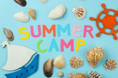 Text SUMMER CAMP from multicolored paper letters and sea scenery against a bright blue background. top view. flat lay stock photos