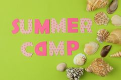 Text SUMMER CAMP of multicolored paper letters and seashells on a bright green background. top view. flat lay. Text SUMMER CAMP of multicolored paper letters and royalty free stock photography