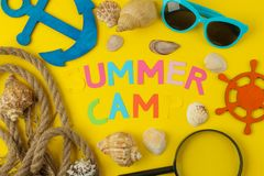 Text SUMMER CAMP of multicolored paper letters and seashells and a decorative steering wheel on a bright yellow background. top vi. Ew. flat lay royalty free stock photos