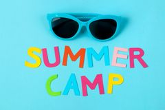 Text SUMMER CAMP of multicolored paper letters and sunglasses on a bright blue background. top view. flat lay stock images