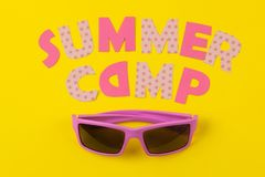 Text SUMMER CAMP of multicolored paper letters and sunglasses on a bright yellow  background. top view. flat lay. Text SUMMER CAMP of multicolored paper letters stock photography