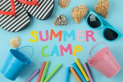 Text SUMMER CAMP of multicolored paper letters and sunglasses, flip flops and crayons against a bright blue background. top view. Flat lay royalty free stock photography