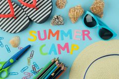 Text SUMMER CAMP of multicolored paper letters and sunglasses, hat and flip flops against a bright blue background. top view. flat. Text SUMMER CAMP of royalty free stock image