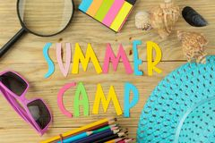 Text SUMMER CAMP of multicolored paper letters and sunglasses and hat on a natural wooden background. top view. flat lay. Text SUMMER CAMP of multicolored paper stock photography