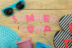 Text SUMMER CAMP of multicolored paper letters and sunglasses and hat on a natural wooden background. top view. flat lay. Text SUMMER CAMP of multicolored paper royalty free stock photo
