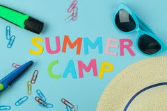 Text SUMMER CAMP of multicolored paper letters and sunglasses, hat and paperclip against a bright blue background. top view. flat. Lay stock photo
