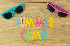 Text SUMMER CAMP of multicolored paper letters and sunglasses on a natural wooden background. top view. flat lay. Text SUMMER CAMP of multicolored paper letters stock photo