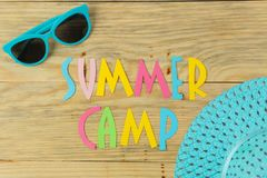 Text SUMMER CAMP of multicolored paper letters and sunglasses on a natural wooden background. top view. flat lay royalty free stock photos