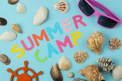 Text SUMMER CAMP of multicolored paper letters and sunglasses and seashells on a bright blue background. top view. flat lay stock photos