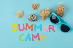 Text SUMMER CAMP of multicolored paper letters and sunglasses and seashells on a bright blue background. top view. flat lay stock photo