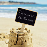 Text summer is here in a signboard topping a sandcastle. Closeup of a sandcastle on the sand of a beach topped with a black signboard with the text summer is stock photos