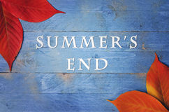 The text summer's end written on wooden, blue background with autumn's leaves in corners. Stock Photography