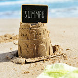 Text summer in a signboard topping a sandcastle Stock Photography