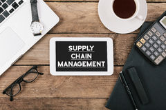 "Text supply chain management on screen of table computer at offi. Screen with ""supply chain management"" text on tablet, Office desk with electronic devices Royalty Free Stock Images"