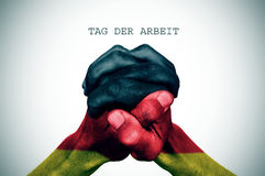 Text tag der arbrit, labour day in German. Man hand patterned with the flag of Germany put together and the text tag der arbrit, labour day in German, with a Royalty Free Stock Photos