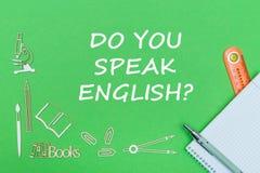Text talar du engelska, träminiatyrer för skolatillförsel, anteckningsbok med linjalen, penna på grön målbräda royaltyfri fotografi