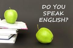 Text talar du engelska, två gröna äpplen, öppna böcker med begrepp royaltyfri bild