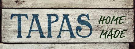 Text tapas homemade in a rustic signboard Stock Images