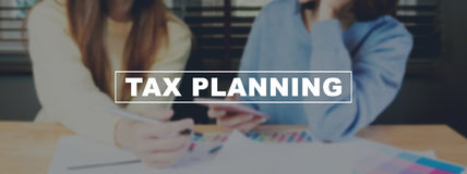 Text Tax planning on background women are working on smartphone. The concept of working with a lot of information. Text Tax planning on background women are Royalty Free Stock Image