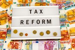 Tax Reform. Text  Tax Reform written on lightbox surrounded with Euro Banknotes Stock Photo