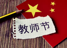 Text Teachers Day in Chinese and flag of China. Closeup of a peace of paper with the text Teachers Day written in Chinese, a pencil and the flag of China, placed royalty free stock images