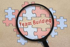 Text Team Building. Written in the place of a missing puzzle under a magnifier Royalty Free Stock Image