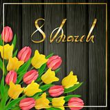 Text 8th March Womens Day on black wooden background with tulips. Golden lettering 8th March International Women`s Day on black wooden background with colored Stock Image
