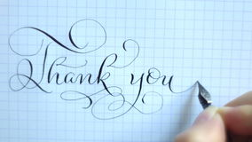 Text thank you with a pen on a sheet of paper. Calligraphy lettering.  stock video