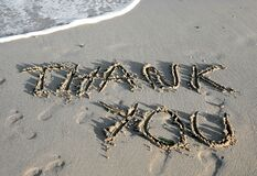 text THANK YOU written on the sand of the beach