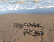 text THANK YOU written on the sand by the sea