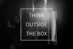 Text Think outside the box over conceptual business scene. With businessman in a shadowy office with a bright white light flare Royalty Free Stock Photos