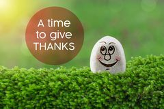 A time to give thanks. The text a time to give thanks with stone smile happy face on green moss and sunshine light background royalty free stock photo